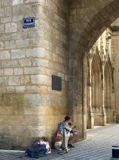 A man and his dog under the arch of Église Catholique Saint-Eloi